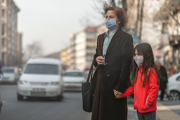 woman are going to work.she wears N95 mask.prevent PM2.5 dust and smog, mother and child wearing a mask to protect their child from air pollution and infectious diseases Photograph by Phynart Studio