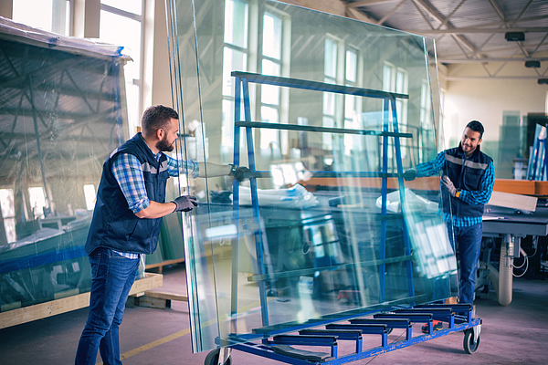 Workers Packaging Glass Sheets In Warehouse Photograph by Bluecinema