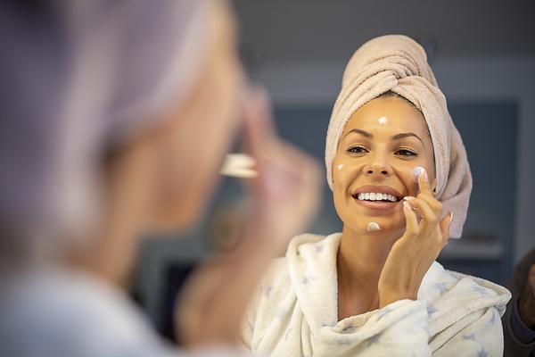 Young woman applying face cream. Photograph by Nikola Ilic