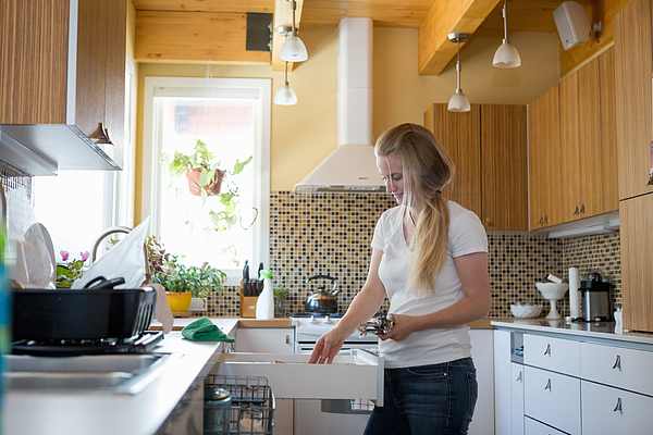 Young woman cleaning kitchen with green cleaning products Photograph by Heshphoto