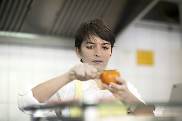 Young woman preparing food in fast food shop Photograph by Sigrid Gombert