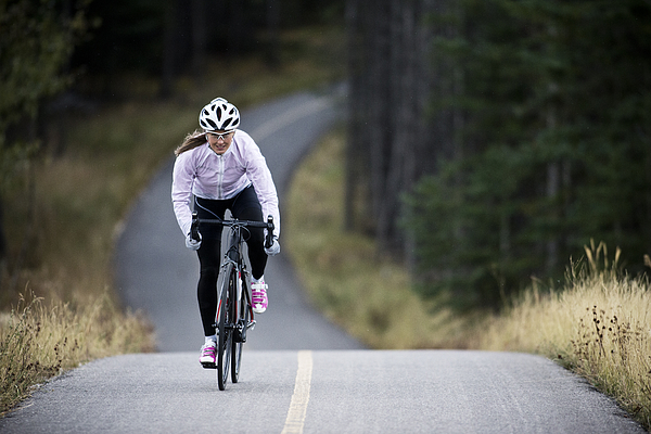 A Woman Rides Her Road Bike Along The Trans Canada Trail Bikepath Near Canmore, Alberta, Canada In The Autumn. Photograph by GibsonPictures