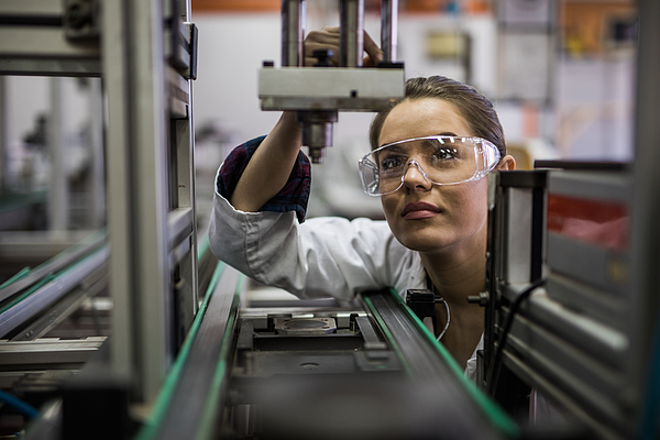 Female engineer examining machine part on a production line. Photograph by Skynesher
