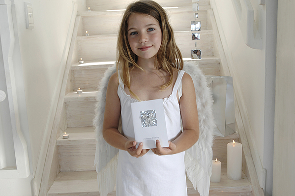 Little girl in an angel costume, holding a Christmas card, indoors Photograph by Pascal Broze