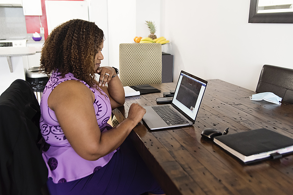 Mature African-American woman working from home in teleconference. Photograph by Martinedoucet