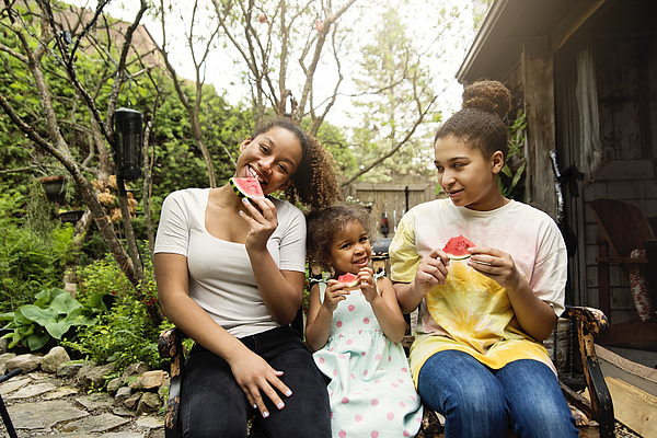 Mixed-race sisters eating watermelon in backyard. Photograph by Martinedoucet
