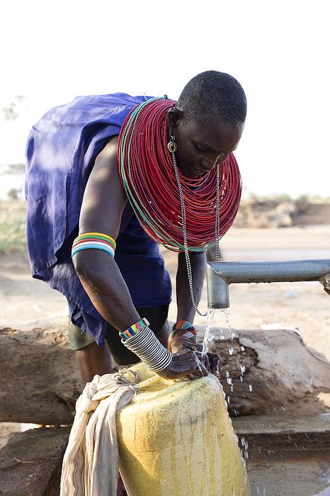 Women collecting clean water from borehole in desert. Samburu. Kenya. Photograph by Hugh Sitton