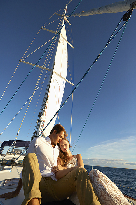 Caucasian couple sitting on yacht deck Photograph by Colin Anderson Productions pty ltd