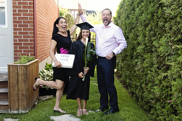 Teenage girl graduation from primary school family portrait in backyard. Photograph by Martinedoucet