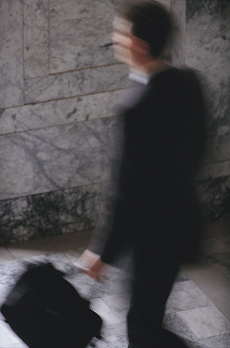 A blurred businessman in a black suit carries a brief case as he walks Photograph by Photodisc