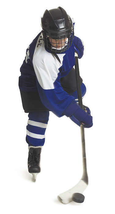 A Child Caucasian Male Hockey Player Dressed  In A Blue White And Black Jersey Skates With His Stick And Puck Photograph by Photodisc