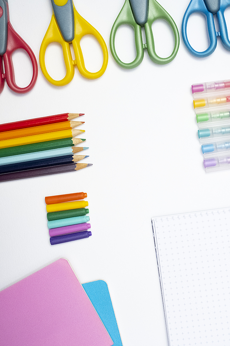 A collection of rainbow coloured school supplies on a white background, portrait format Photograph by Catherine MacBride