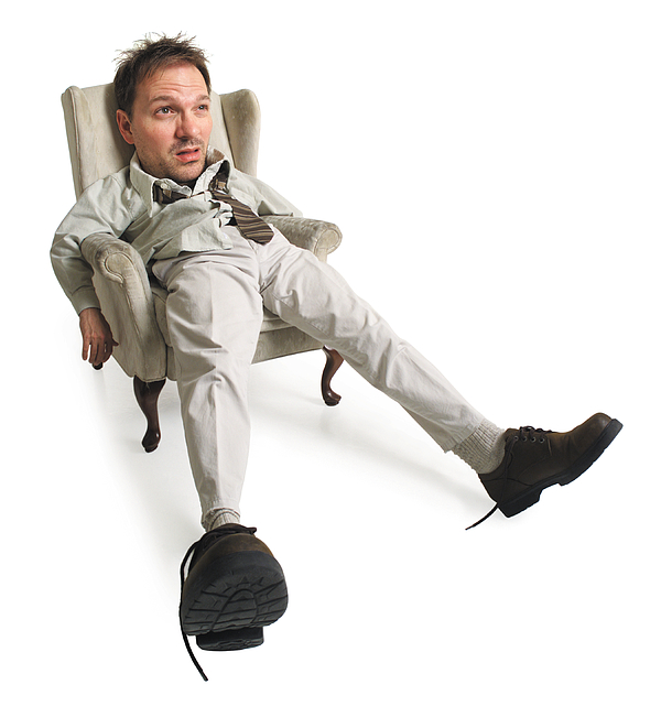 A Frazzled Caucasian Man Sits In His Chair And Sticks His Feet Out While Looking Exhausted Photograph by Photodisc