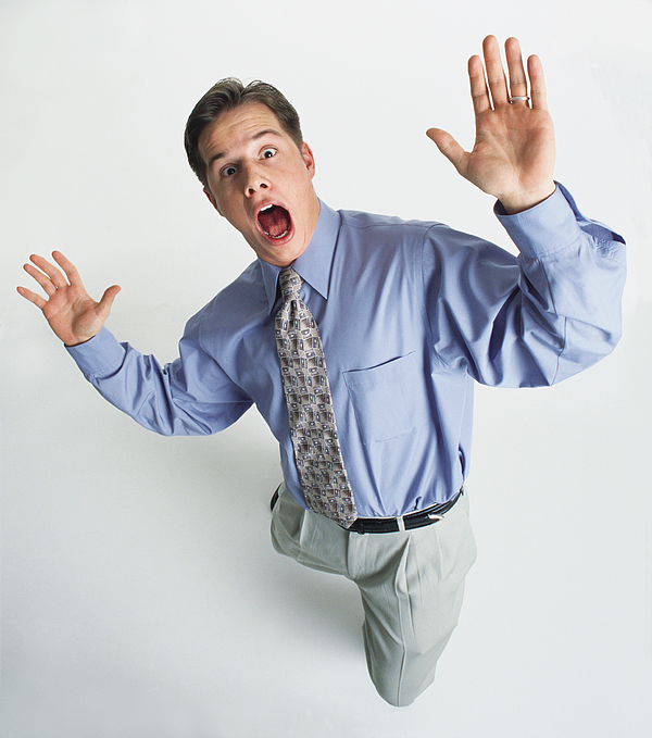 A Handsome Young Caucasian Man In A Blue Dress Shirt And Tan Pants Is Looking Up Into The Camera With A Shocked Expression On His Face And His Hands Out In A Suprised Gesture Photograph by Photodisc