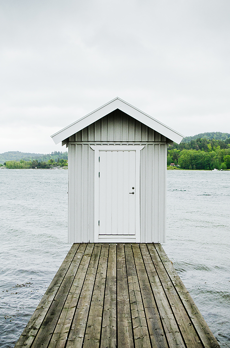 A hut at the end of a wooden lake pier. Photograph by Roman Pretot