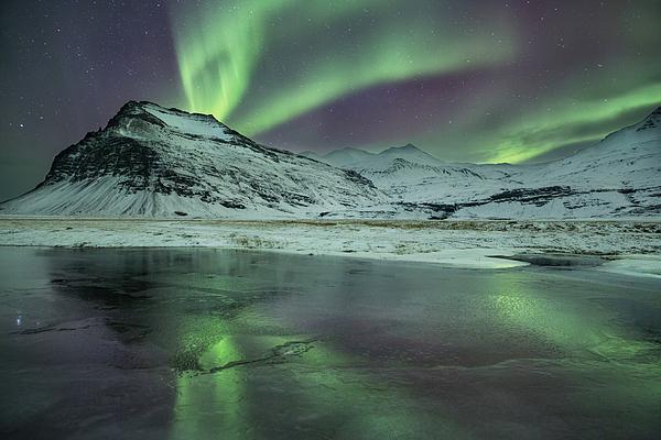 A lake reflects the aurora borealis. Photograph by Alex Saberi