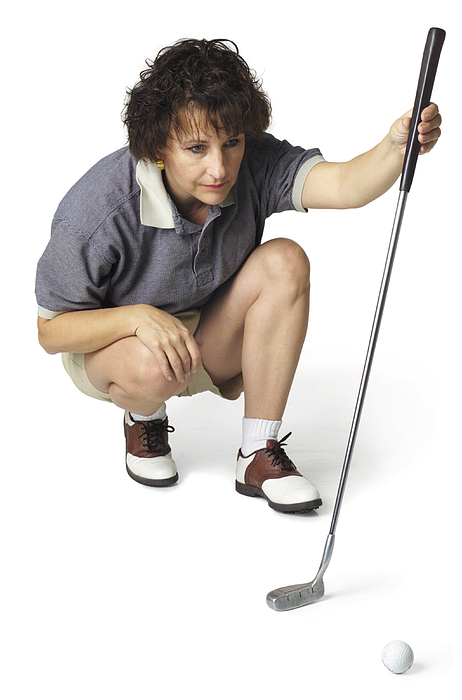 A Middle Age Caucasian Female Golfer In A Stripped Shirt Crouches Down With Her Putter And Lines Up A Shot Photograph by Photodisc