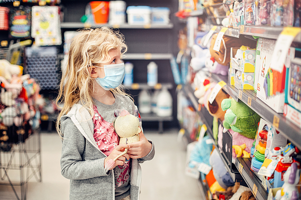 A new normal. Caucasian blonde girl in sanitary face mask shopping at toy store. Child wearing protective mask against coronavirus. Safety, health protection during covid-19 quarantine. Photograph by ~UserGI15613517