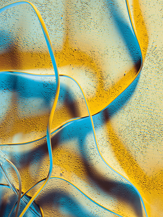 A Series Of White Wires Gives Off Yellow And Blue Shadows Photograph by Photodisc