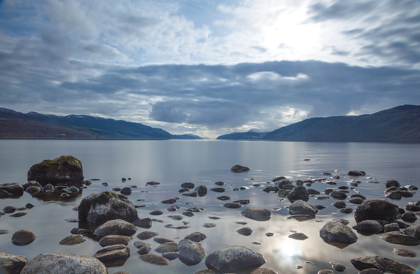 A view across Loch Ness looking down the length of the lake with rocks inn the foreground and dark clouds above, in Scotland Photograph by Luke Richardson