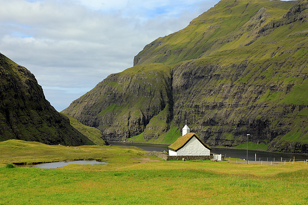 A white stone church with a grassy roof above a bay between high mountains Photograph by Rainer Grosskopf