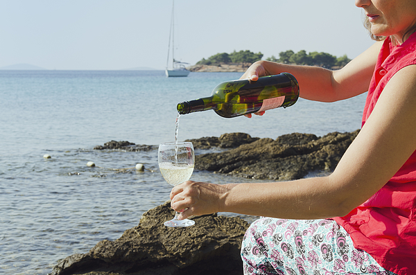 A woman pouring wine into a glass by the sea Photograph by Otto Stadler