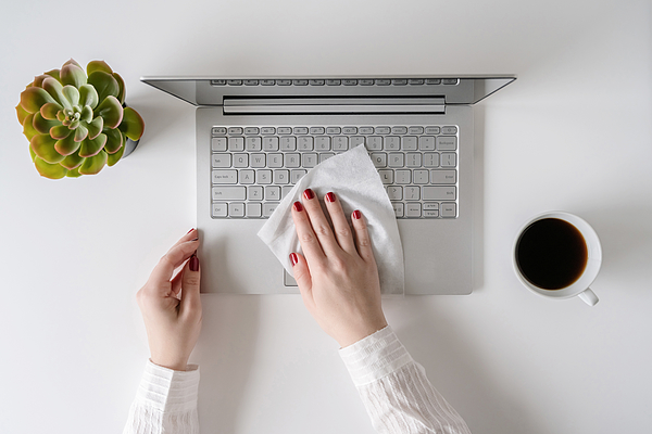 A woman worker cleaning with antivirus wet wipe a laptop and a working office desk before starting work for protect herself from bacteria and virus. Photograph by FTiare
