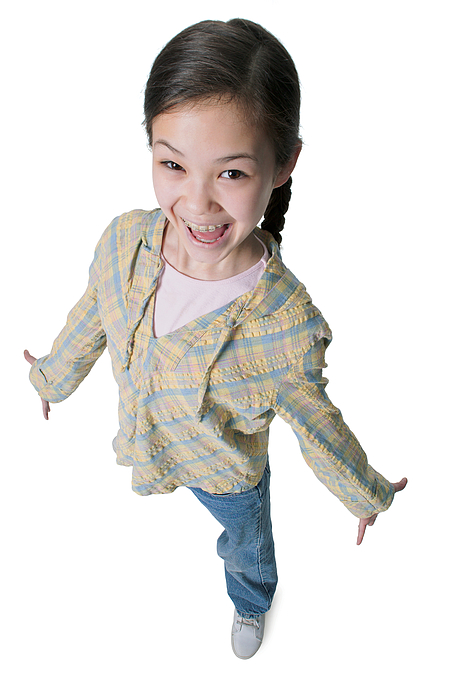 A Young Asian Girl In Jeans And A Green Shirt As She Spreads Out Her Arms And Smiles Up Into The Camera Photograph by Photodisc