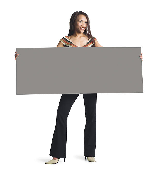 A Young Attractive African American Girl In Black Pants And Striped Blouse Holds A Blank Sign In Front Of Her With Both Hands Photograph by Photodisc