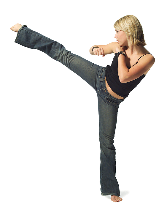 A Young Caucasian Blonde Woman In Jeans And A Black Tank Top Strikes A Martial Arts Pose Photograph by Photodisc