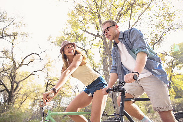 A young, happy man and woman riding bicycles in a park for fitness Photograph by Robb Reece
