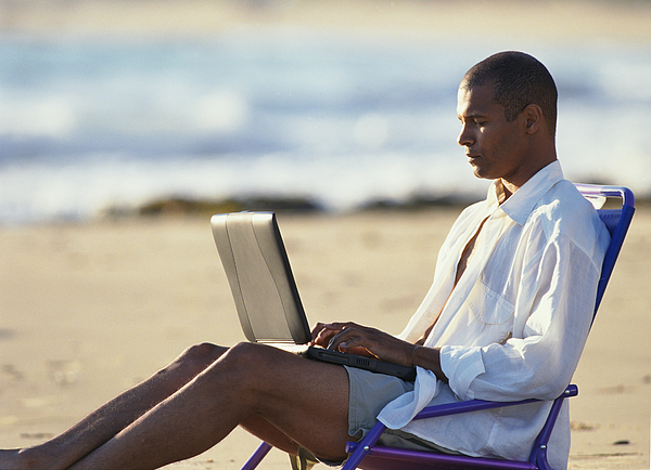 A Young Man In Tan Shorts And A White Oxford Shirt Is Reclining In A Beach Chair Typing In To A Laptop Computer Photograph by Photodisc
