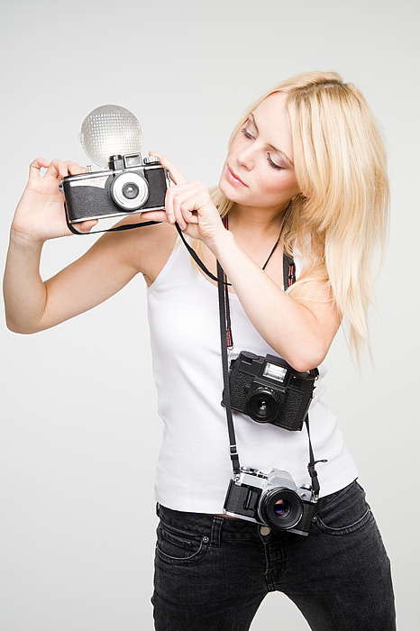 A young woman taking pictures Photograph by Image Source