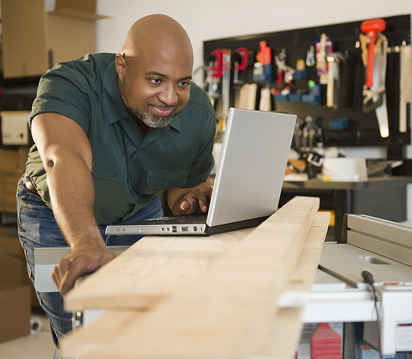 African American carpenter using laptop in workshop Photograph by JGI/Jamie Grill