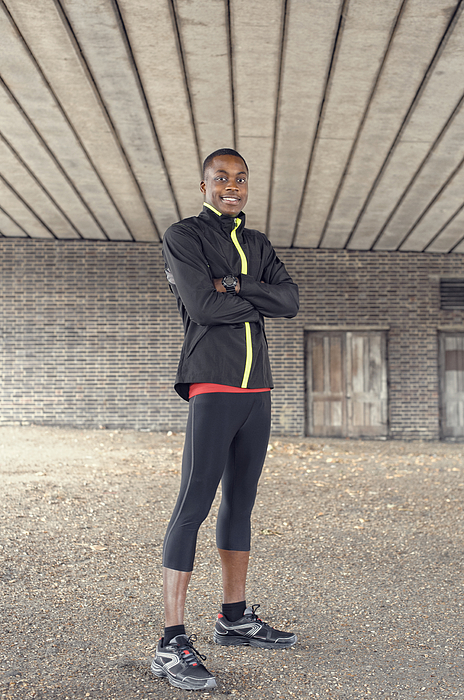 African American runner standing under concrete structure Photograph by Jacobs Stock Photography Ltd