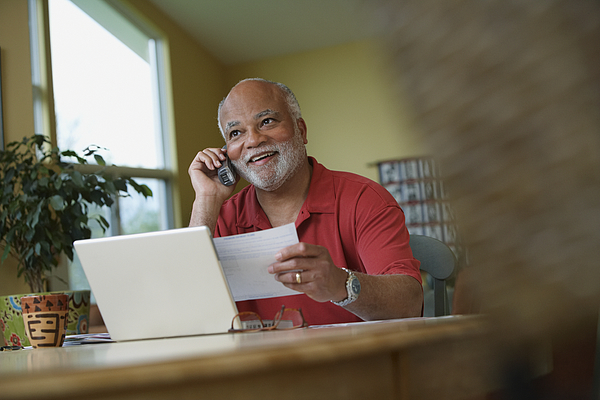 African man talking on telephone while paying bills Photograph by Jon Feingersh Photography Inc
