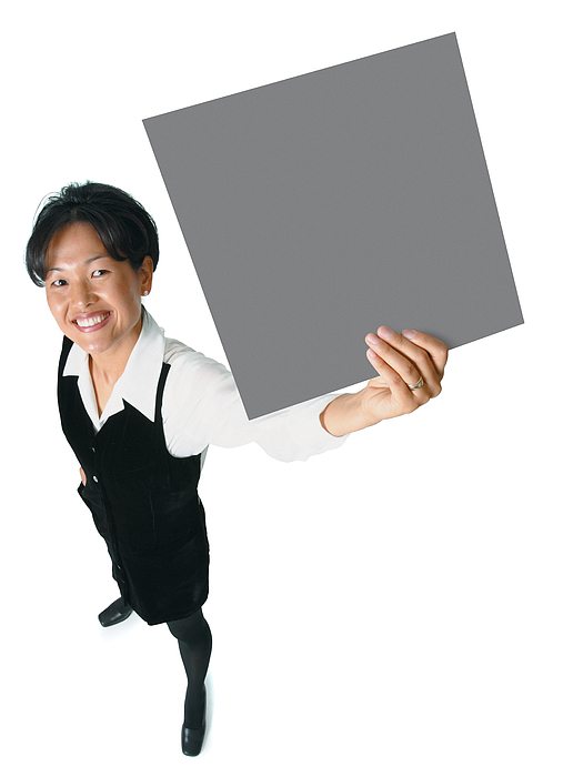 An Adult Asian Woman In A Black Business Outfit Holds A Sign Up To The Side As She Smiles Up Into The Camera Photograph by Photodisc