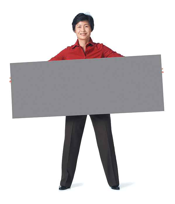 An Adult Asian Woman In A Dark Grey Pants With A Red Blouse Holds A Large Sign In Front Of Herself Photograph by Photodisc