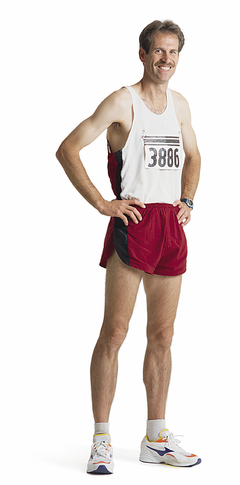 An Adult Caucasian Male Marathon Runner In Red Shorts And A White Tank Stands Smiling With Hands On Hips Photograph by Photodisc