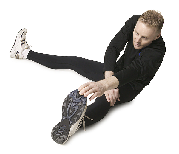 An Adult Caucasian Man In A Black Running Outfit Stretches Out And Prepares For A Jog Photograph by Photodisc