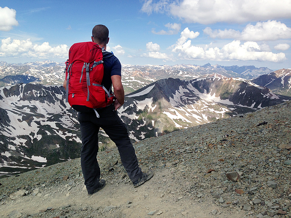 An adult male looks out over a mountain range alone on a remote mountain trail Photograph by Robb Reece