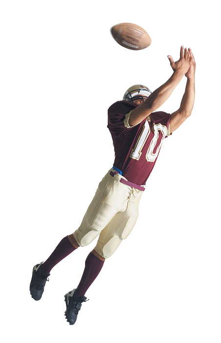 An African American Football Player In A Red And White Uniform Is Jumping Up With Arms Outstretched To Catch A Football Photograph by Photodisc