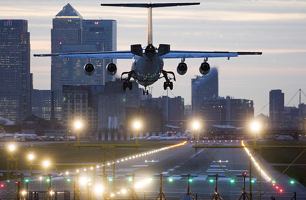 An airplane lands at London City airport with Canary Wharf i Photograph by Bloomberg