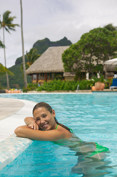 An Attractive Caucasian Woman Leans Against The Edge Of A Swimming Pool At A Tropical Resort Photograph by Photodisc