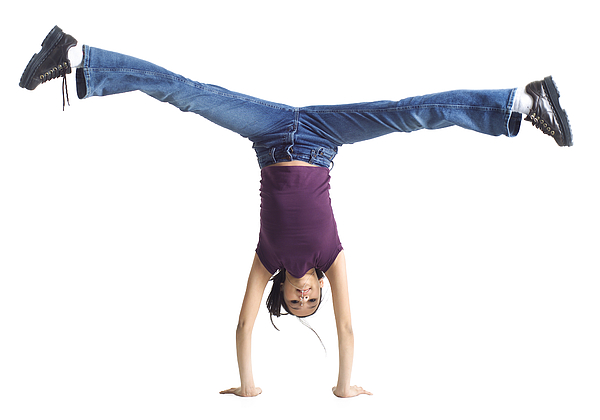 An Ethnic Teenage Girl In Jeans And A Purple Shirt Does A Cartwheel Photograph by Photodisc