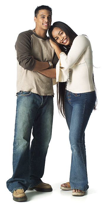 An Ethnic Teenage Male In Jeans And A Tan Shirt Stands With His Younger Sister As They Smile Photograph by Photodisc