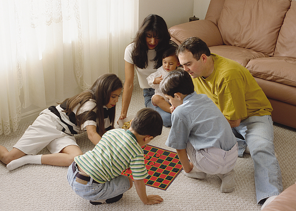 An Ethnically Mixed Family Sits In A Circle Playing A Game Photograph by Photodisc