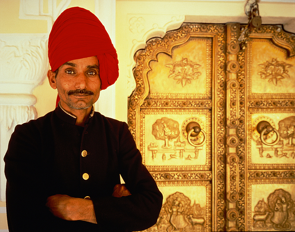 An Indian guardsman standing in front of a golden door, India, Jaipur, City Palace, half port Photograph by Hugh Sitton
