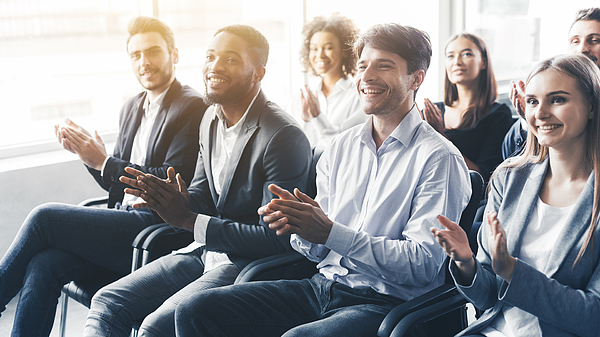 Applauding to speaker. Group of happy business people in conference hall Photograph by Prostock-Studio