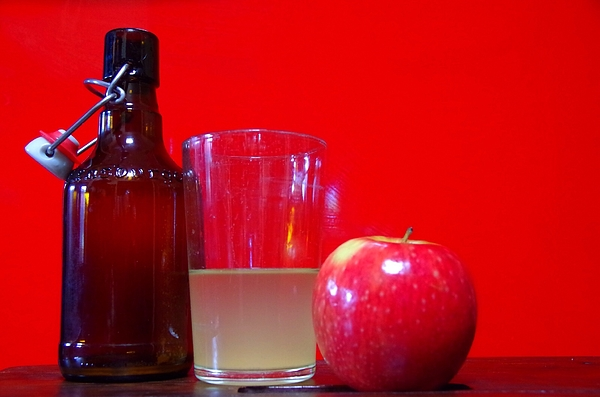 Apple With Juice In Drinking Glass And Bottle Against Red Wall Photograph by Denice Tyler / EyeEm